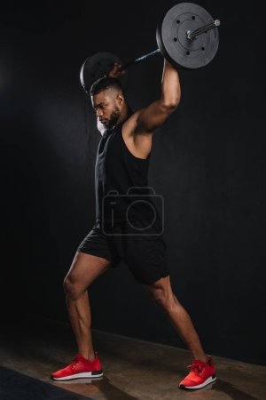 full length view of muscular young african american sportsman lifting barbell on black