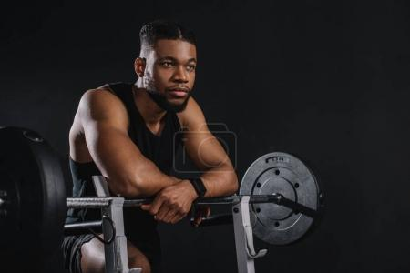 muscular young african american sportsman leaning at barbell and looking away on black