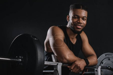 muscular young african american sportsman leaning at barbell and smiling at camera on black