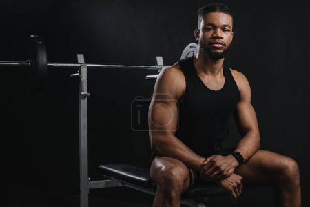 athletic young african american man in sportswear sitting and looking at camera in gym