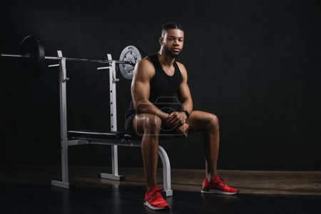 muscular young african american man in sportswear sitting and looking at camera in gym