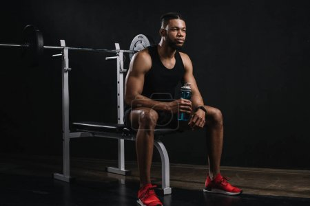 young african american sportsman holding bottle of water and looking away on black