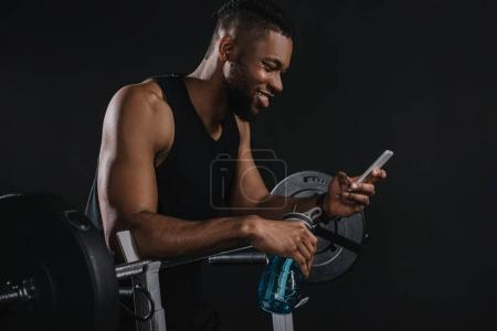 smiling young african american sportsman holding bottle of water and using smartphone
