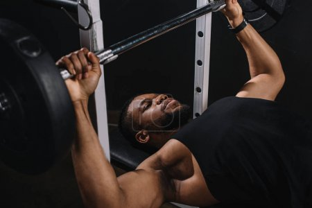 muscular young african american man in sportswear lifting barbell