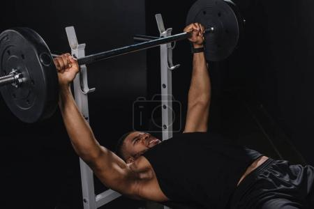 muscular young african american sportsman lifting barbell