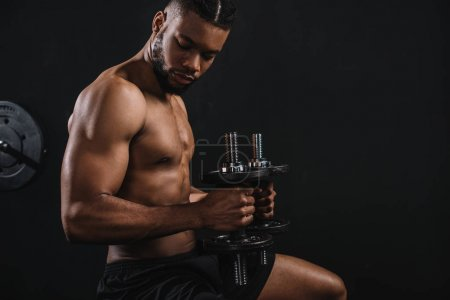 side view of muscular shirtless young african american man exercising with dumbbells on black