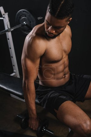 high angle view of muscular shirtless african american man training with dumbbell