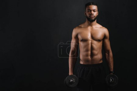 muscular shirtless african american man holding dumbbells and looking at camera isolated on black