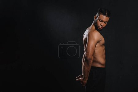 side view of muscular young african american man stretching hands isolated on black