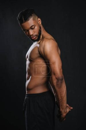 side view of shirtless muscular young african american man stretching hands isolated on black
