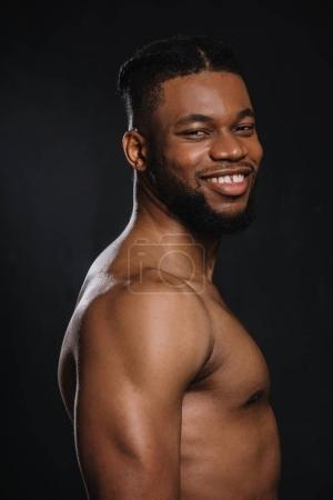 Foto de Retrato de guapo sin camisa muscular afroamericano joven sonriendo a cámara aislada en negro - Imagen libre de derechos