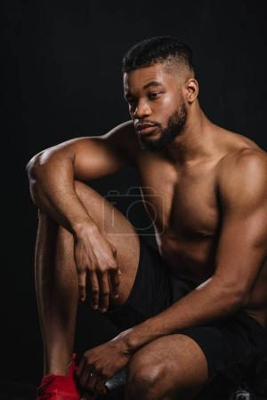 Photo for Pensive shirtless young african american sportsman sitting and looking away on black - Royalty Free Image