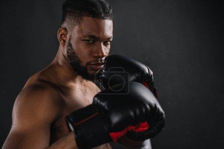 Photo pour Jeune boxeur afro-américain torse nu dans les gants de boxe en regardant caméra isolée sur fond noir - image libre de droit