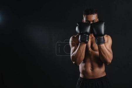 young shirtless african american boxer in boxing gloves looking at camera isolated on black