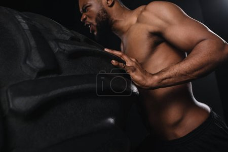 low angle view of muscular young african american sportsman lifting tire on black