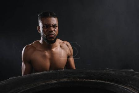 Photo for Muscular young african american sportsman lifting tire on black - Royalty Free Image