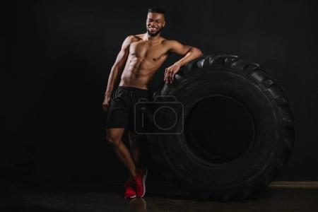 muscular shirtless young african american sportsman leaning at tyre and smiling at camera on black
