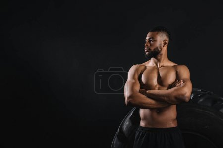 Photo for Muscular shirtless african american sportsman standing with crossed arms near big tyre and looking away isolated on black - Royalty Free Image