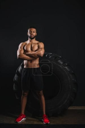 Photo for Full length view of shirtless african american sportsman standing with crossed arms near big tyre and looking at camera on black - Royalty Free Image