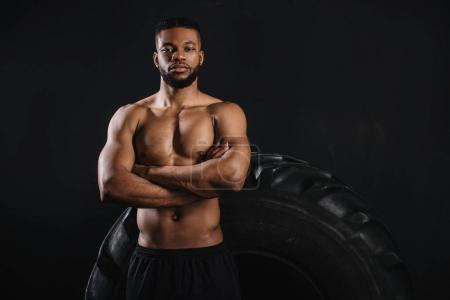 muscular shirtless african american sportsman standing with crossed arms near big tyre and looking at camera isolated on black