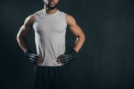 cropped shot of muscular african american kickboxer in gloves standing with hands on waist isolated on black