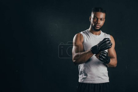 Photo for Young african american kickboxer wearing gloves and looking at camera isolated on black - Royalty Free Image