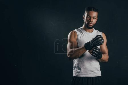 young african american kickboxer wearing gloves and looking at camera isolated on black