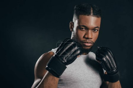Photo for Serious young african american kickboxer in gloves looking at camera isolated on black - Royalty Free Image