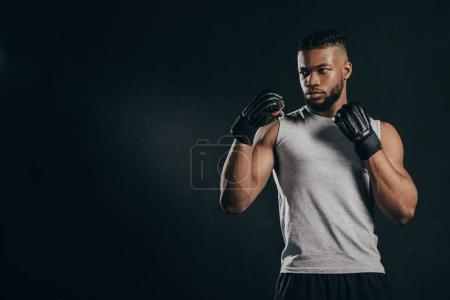 Photo for Serious muscular young african american sportsman in gloves training isolated on black - Royalty Free Image