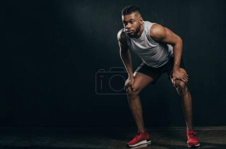 full length view of athletic young african american man in sportswear looking away on black