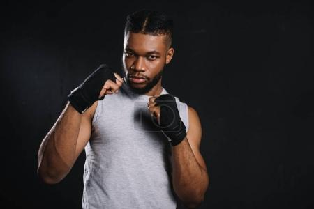 serious young african american fighter looking at camera isolated on black