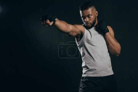 Photo for Serious young african american kickboxer exercising isolated on black - Royalty Free Image