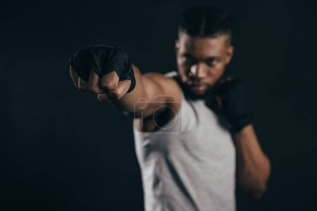 Photo for Close-up view of young african american kickboxer training on black - Royalty Free Image