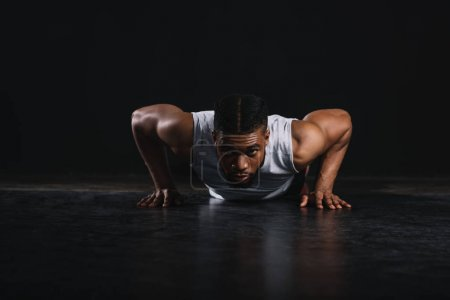 Photo for Young muscular african american man in sportswear doing push-ups and looking at camera - Royalty Free Image