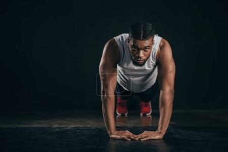 young african american sportsman doing plank position and looking at camera on black