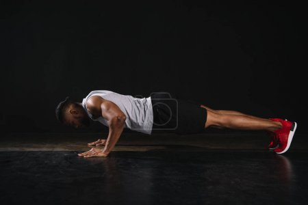 side view of young african american sportsman doing push-ups on black