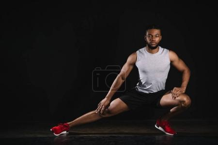 athletic young african american man in sportswear exercising and looking at camera on black