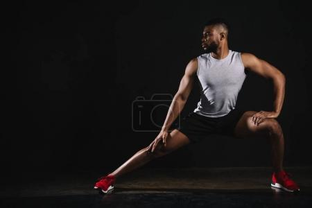 Photo for Athletic young african american man in sportswear exercising and looking away on black - Royalty Free Image
