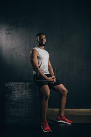 full length view of young athletic african american man in sportswear sitting and looking at camera on black