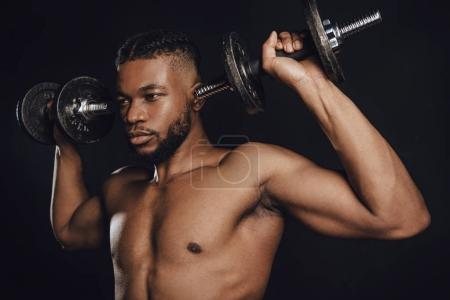 Photo for Muscular shirtless african american sportsman training with dumbbells and looking away isolated on black - Royalty Free Image