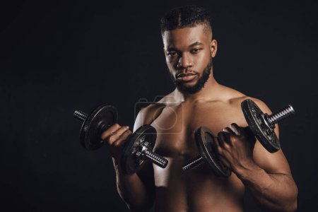 muscular shirtless african american sportsman training with dumbbells and looking at camera isolated on black