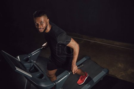 high angle view of young african american sportsman training on treadmill and looking at camera