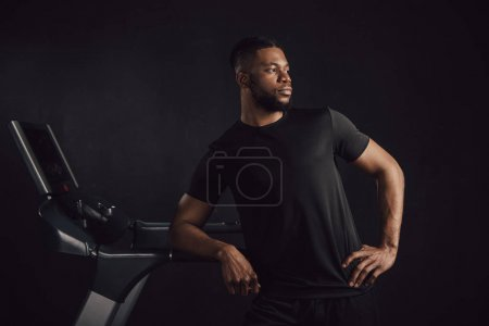 athletic young african american man leaning at treadmill and looking away isolated on black