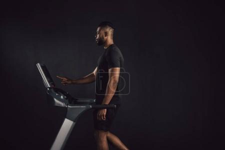 side view of athletic young african american man exercising on treadmill isolated on black