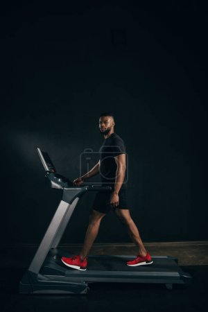 young african american sportsman exercising on treadmill and looking at camera on black