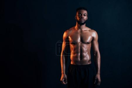 Photo for Handsome shirtless muscular african american man standing and looking at camera isolated on black - Royalty Free Image