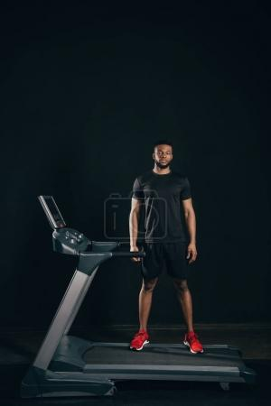 young african american sportsman standing on treadmill and looking at camera on black