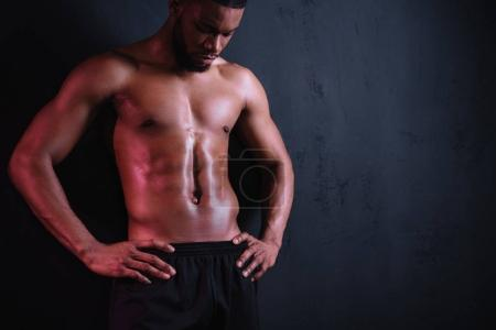 muscular bare-chested african american man standing with hands on waist and looking down on black