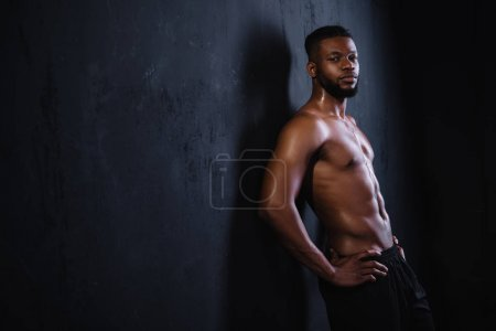 shirtless muscular young african american man standing with hands on waist and looking at camera on black
