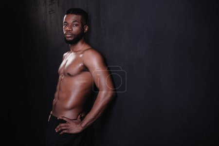 handsome shirtless muscular young african american man looking at camera on black